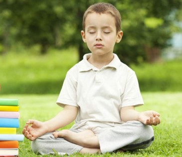 Little boy in zen meditation preparing to be good student
